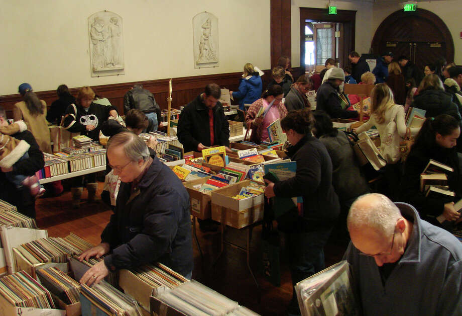 Patrons browse through books, recordings and other goods at last year's Mid-Winter Book Sale at the Pequot Library. The popular, four-day event kicks off Saturday morning. On the final morning, bargain hunters can pack a bag of books for $5. Photo: Contributed Photo