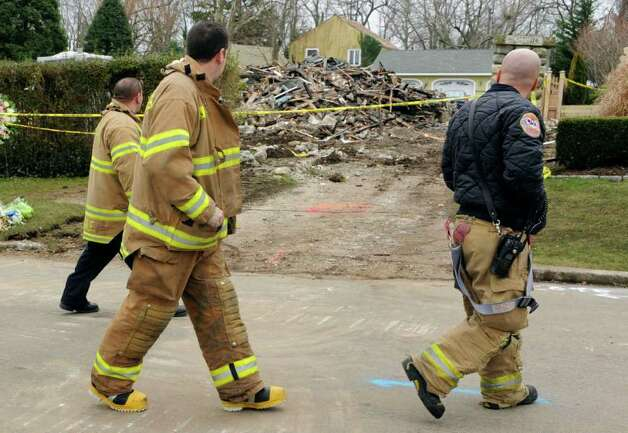 Firefighters look at the charred remains Madonna Badger's home in Stamford, Conn., Tuesday, Dec. 27, 2011.   A fire killed Badger's three daughters and parents early Christmas morning.  (AP Photo/Jessica Hill) Photo: Jessica Hill, Associated Press / AP2011