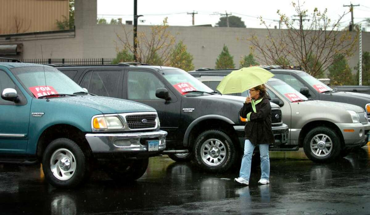 Linda Cappello, of Bridgeport, browses the selection of used vehicles being sold in an online auction by the city of Bridgeport during a preview Thursday Oct. 15, 2009 at the Public Works garage on Housatonic Avenue. The auction of surplus vehicles includes SUVs, passenger cars and work vehicles and will be online for one week.