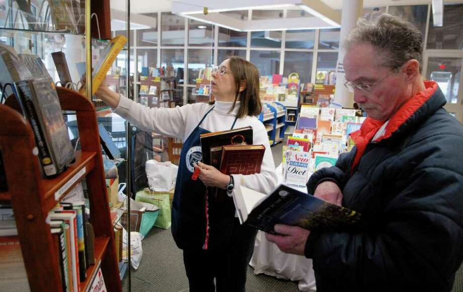 Volunteer Linda Milano shelves books as Abe Yellen checks out some of the new titles at the Friends of the Library bookstore at the Ferguson Library's Harry Bennett branch in Stamford, Conn. on Friday January 13, 2012. Photo: Dru Nadler / Stamford Advocate Freelance