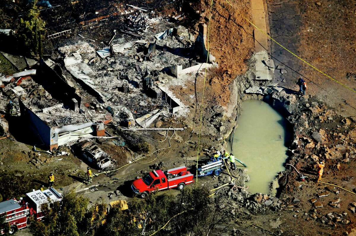 Emergency crews comb through the rubble of burned homes next to a crater that was caused by the explosion of a 30-inch natural gas pipeline in San Bruno.Water is pumped from the crater caused by the explosion of a 30-inch natural gas pipeline in San Bruno.
