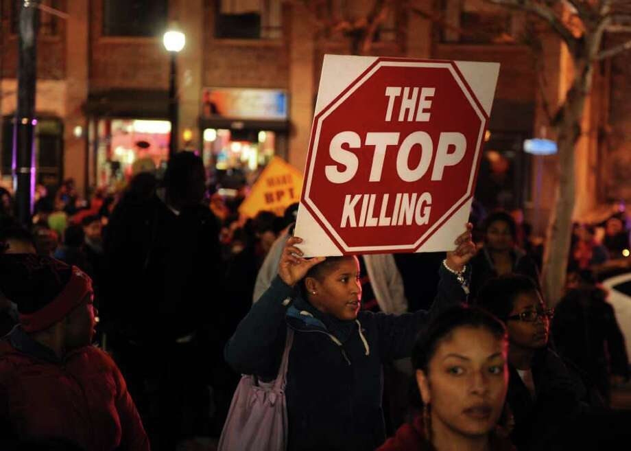 Fifteen-year-old Tanaisha Bagley, of Bridgeport, carries a sign Wednesday, Jan. 11. 2012 during an anti-violence rally on the steps of City Hall Annex in Bridgeport, Conn.  Hundreds of residents marched from the East End Police Substation on Stratford Avenue to City Hall in response to the shooting of 14-year-old Justin Thompson. Photo: Autumn Driscoll / Connecticut Post