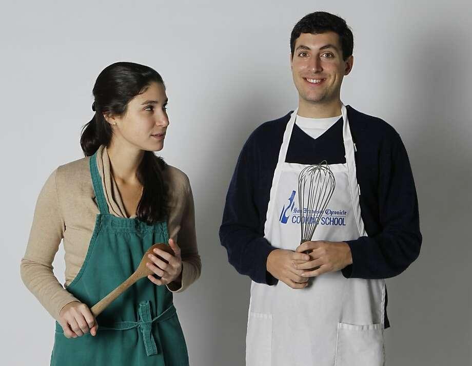 Sophie Brickman teaches her boyfriend Dave Eisenberg how to cook. Photo: Paul Chinn, The Chronicle