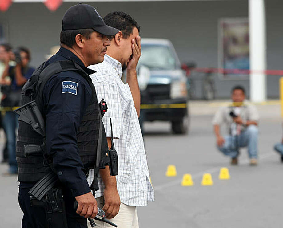 A relative of photojournalist Luis Carlos Santiago, of El Diario newspaper, who was killed by gunmen in a parking lot in Mexico's most dangerous city of Ciudad Juarez, on the US border, cries next to a policemen at the scene of the crime on September 16,2010. A colleague of Santiago from the same newspaper was seriously hurt in the attack. Photo: Afp, AFP/Getty Images