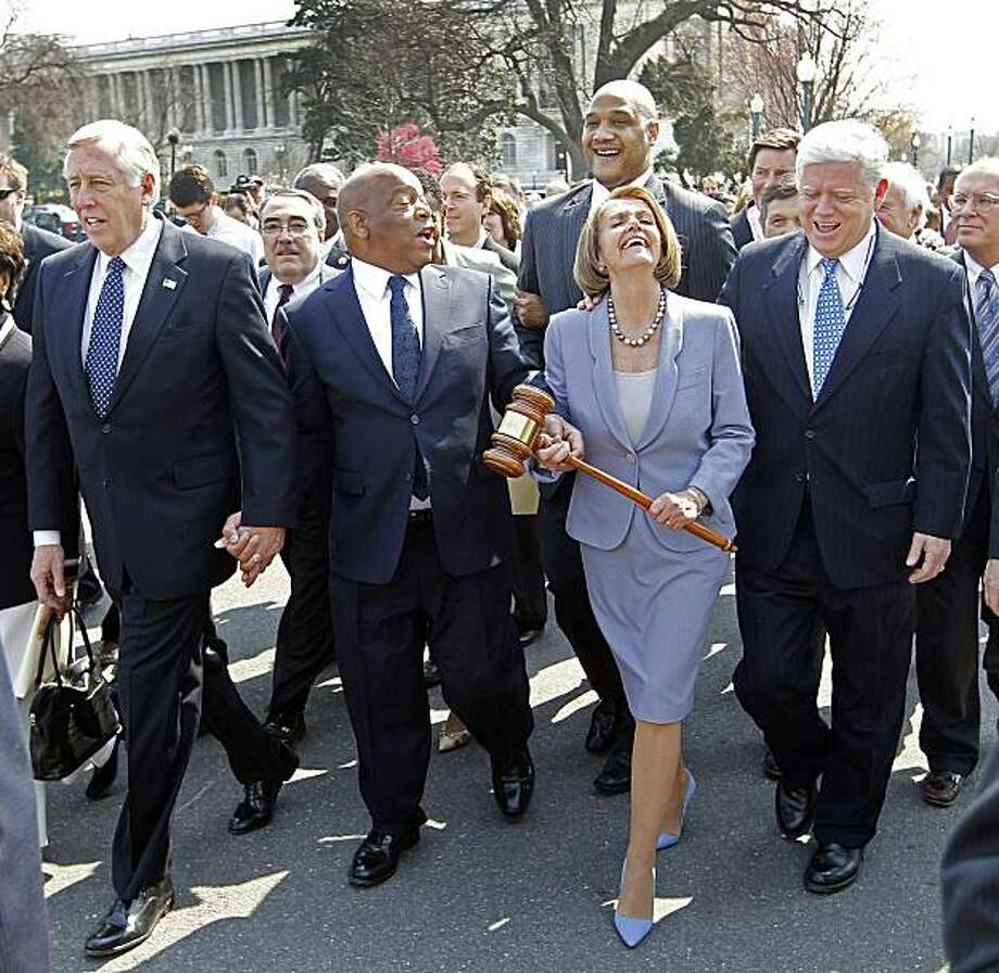 Speaker Nancy Pelosi of California holding the gavel used to pass Medicare Reform, laughs as she walks across the street and into the U.S. Capitol as the House prepares to vote on health care reform in the U.S. Capitol in Washington, Sunday, March 21, 2010. Walking with Speaker Pelosi are from left, Rep. Steny Hoyer, D-Md., Rep. John Lewis, D-Ga., and Rep. John Larson, D-Conn. Photo: Charles Dharapak, AP