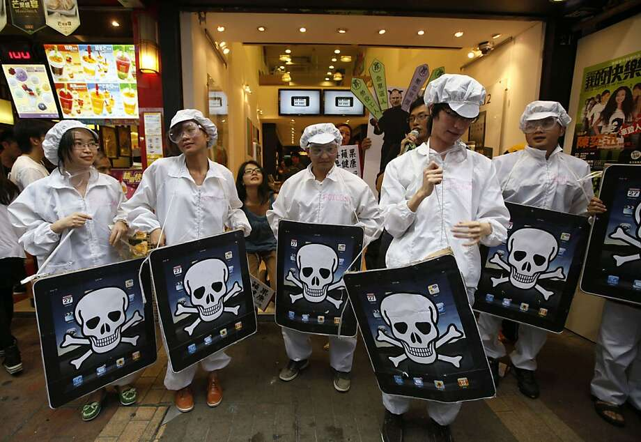 FILE - In this file photo taken Saturday, May 7, 2011, local and mainland Chinese university students, dressed as the Foxconn workers, hold mock iPads with a skeleton print outside an Apple Premium Reseller shop in Hong Kong. An explosion that occurred onMay 20, 2011, at one of two factories that make Apple's new iPad 2 highlights the risks of a global manufacturing strategy that has cut costs but concentrates production in a few locations. Photo: Kin Cheung, AP