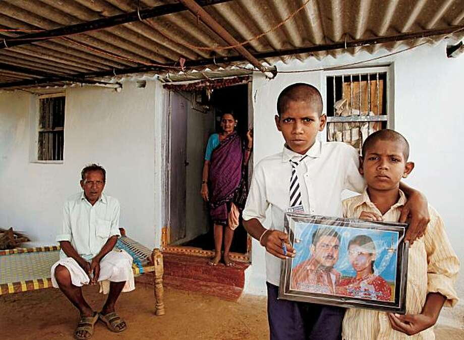 Brothers, right, with grandparents in background, hold a picture of their deceased parents outside their home in Mondrai, 80 kilometers (50 miles) from the city of Warangal, in the state of Andhra Pradesh, India, on Thursday, Nov. 18, 2010. After being pressured for money by lenders, their mother set herself on fire and her husband died from burns trying to smother the flames. Andhra Pradesh, where three-quarters of the 76 million people live in rural areas, suffered a total of 14,364 suicide cases in thefirst nine months of 2010, according to state police. Photographer: Namas Bhojani/Bloomberg Markets via Bloomberg EDITOR'S NOTE: IMAGE AVAILABLE FOR ONE-TIME USE ONLY TO ACCOMPANY BLOOMBERG MARKETS MAGAZINE STORY, SUICIDES AMONG BORROWERS, BY YOOLIM L Photo: Namas Bhojan, Bloomberg News