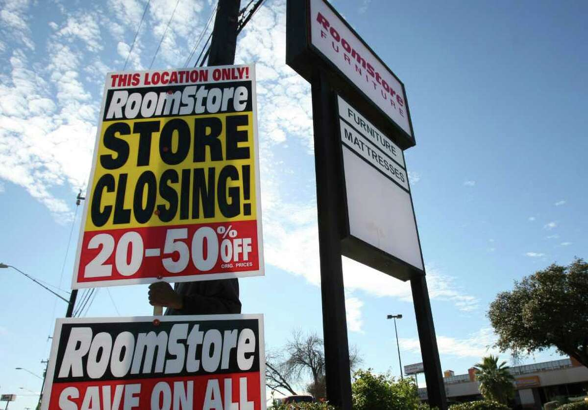 Travis Boykin holds a sign on Perrin Beitel announcing a closing sale at The Room Store. The company has filed for bankruptcy and will be closing five stores in San Antonio.