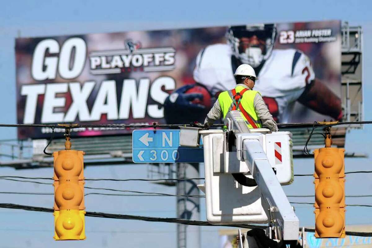 A billboard supporting the NFL Houston Texans looms over a man working on streetlights on Broadway Dec. 13, 2012.