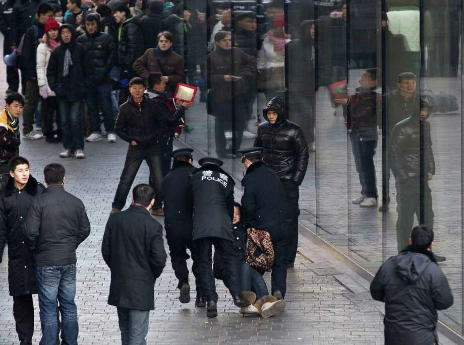 A woman is dragged away by police after she refused to leave an Apple store in Beijing on Friday. A crowd became unruly after the store refused to open. Photo: Andy Wong / AP