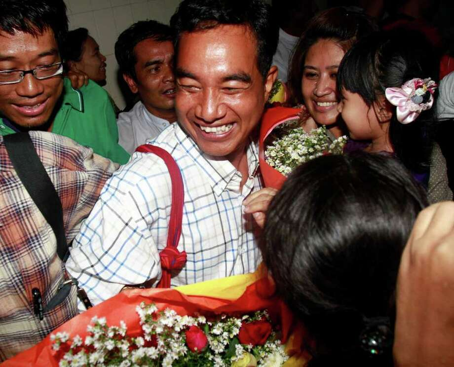 Zaw Thet Htway, center, a journalist who was arrested in the 2007 Saffron Revolution, is welcomed by colleagues after being released from jail Friday. Photo: Khin Maung Win / AP