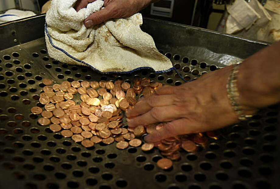 To rid the coins of the birdshot, Rob Holsen runs them over a large sifting device Monday December 20, 2010. Rob Holsen may be the only professional coin washer in the United States.  He washes coins for the Westin St. Francis Hotel in Union Square, San Francisco, Calif., a tradition which began to keep ladies white gloves from getting tarnished back in the 1930s. Photo: Brant Ward, The Chronicle