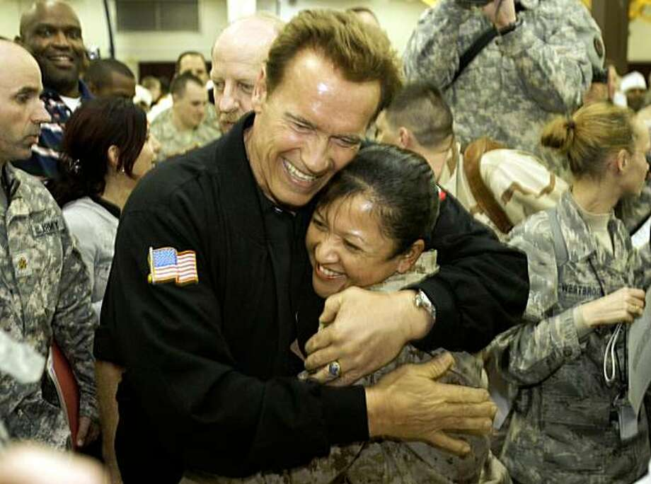 California's Governor Arnold Schwarzenegger hugs a US soldier during his visit to Camp Victory on the outskirts of Baghdad on November 16, 2009. Schwarzenneger flew into Iraq on a morale-boosting visit for US troops, drawing cheers from servicemen and women. AFP PHOTO / ALI AL-SAADI (Photo credit should read ALI AL-SAADI/AFP/Getty Images) Photo: Ali Al-Saadi, AFP/Getty Images