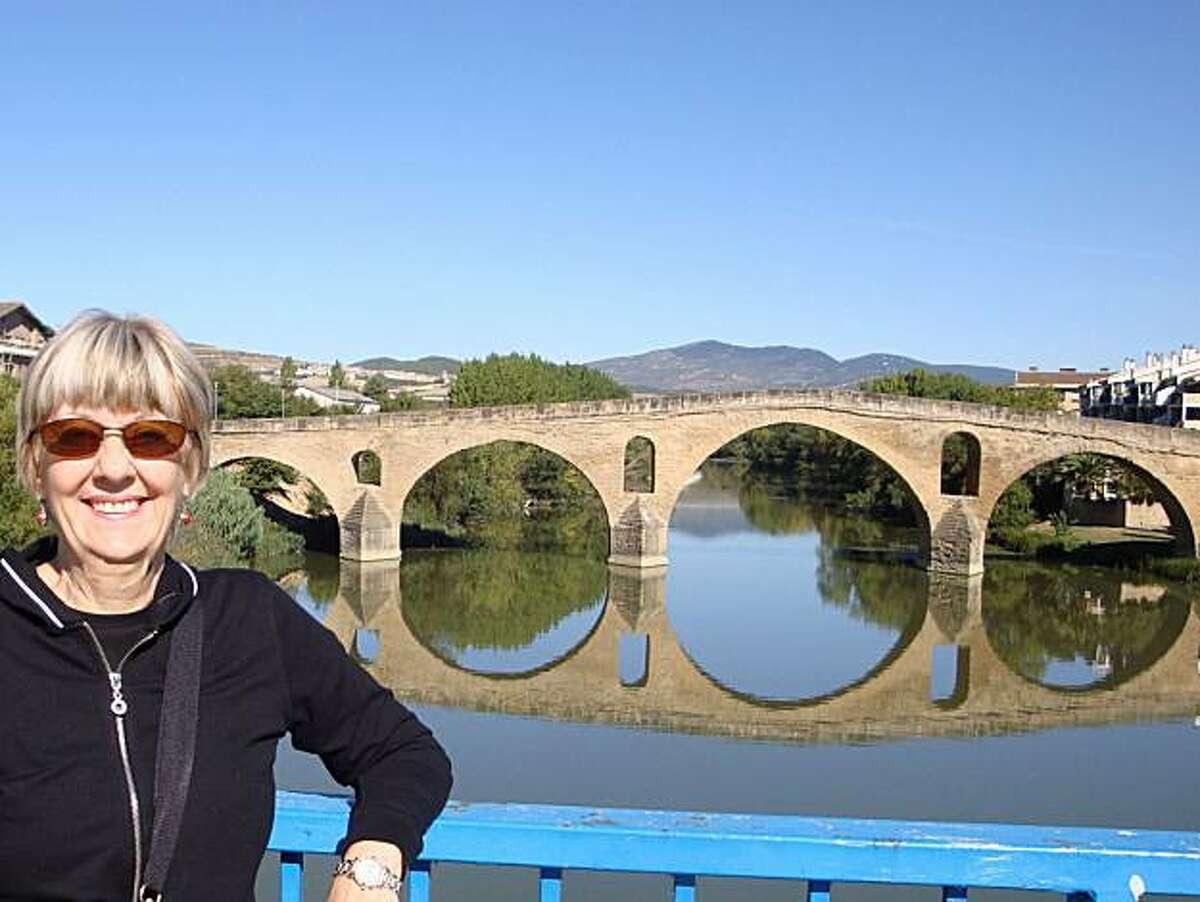 Julie Grimes of Belmont stands near the medieval pilgrimage bridge at Puente La Reina, Spain.