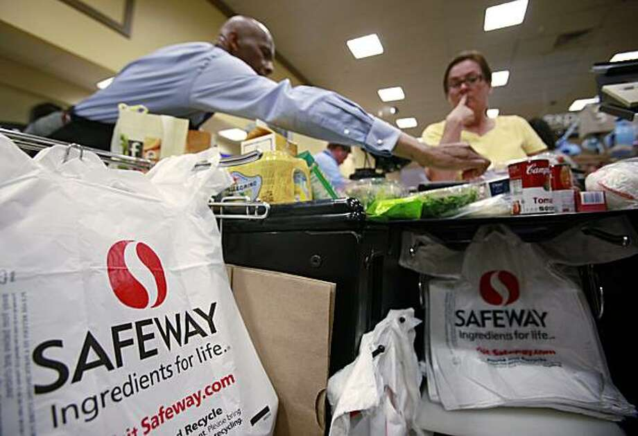 In this June 21, 2010 photo, a Safeway employee, left, bags items for a customer in San Ramon, Calif. National grocery operator Safeway Inc.'s second-quarter net income fell 40 percent and the company lowered its outlook on Thursday, July 22, 2010, in theface of tough competition and declining retail prices. Photo: Paul Sakuma, Associated Press