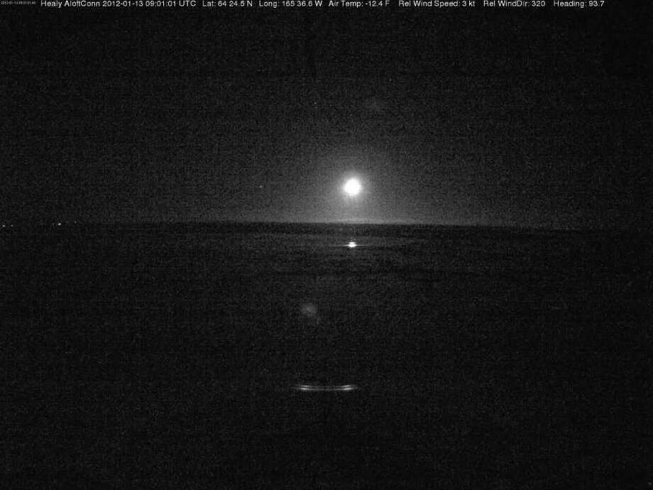 This image provided by the U.S. Coast Guard from the bridge camera aboard the Ice Breaker Healy taken at 4:01 a.m. EST shows lites on the shore line as the Healy and the tanker approach Nome Alaska Friday Jan. 13, 2012. At the time of this image the Healy was 9.2 miles from Nome. (AP Photo/US Coast Guard) / US Coast Guard