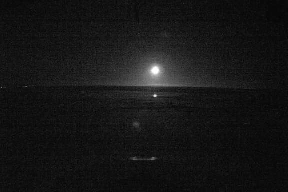 This image provided by the U.S. Coast Guard from the bridge camera aboard the Ice Breaker Healy taken at 4:01 a.m. EST shows lites on the shore line as the Healy and the tanker approach Nome Alaska Friday Jan. 13, 2012. At the time of this image the Healy was 9.2 miles from Nome. (AP Photo/US Coast Guard)