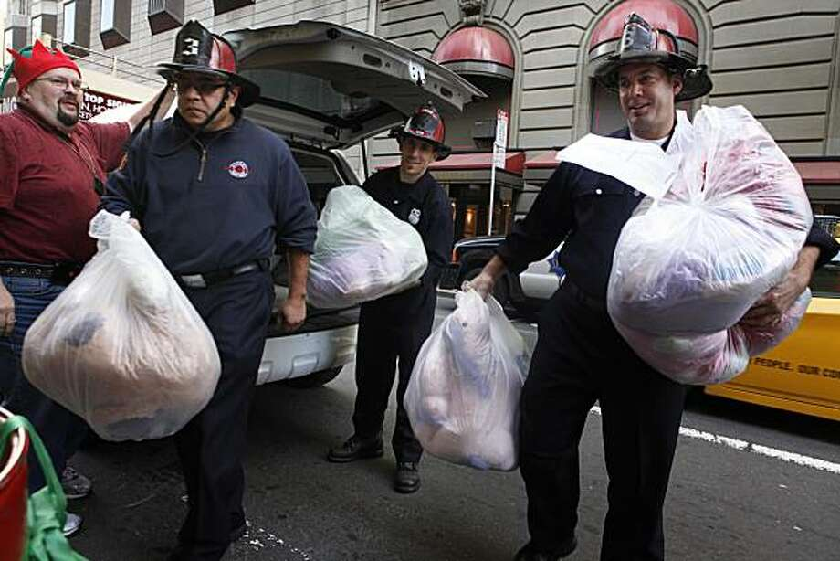 San Francisco Firefighters Romon Baretto, Kailin Waterman and Matt Scola pull donated toys from the back of Bernie Wehman's Luxor Cab during a last minute  rush for the firefighter's toy drive at Lefty O'Doul's on Friday Dec. 24, 2010 in San Francisco, Calif. Throughout the month of December toys are being collected and distributed to kids in need though out the city. Photo: Mike Kepka, The Chronicle