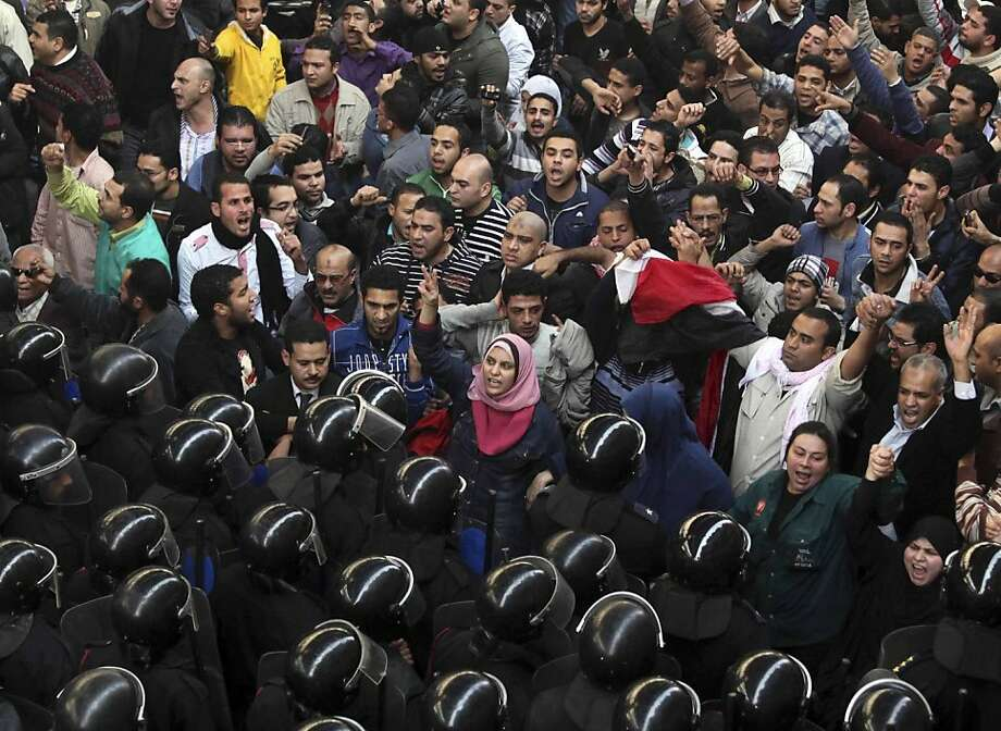 Egyptian protesters face anti-riot policemen in Cairo, Egypt, Friday, Jan. 28, 2011. The Egyptian capital Cairo was the scene of violent chaos Friday, when tens of thousands of anti-government protesters stoned and confronted police, who fired back with rubber bullets, tear gas and water cannons. It was a major escalation in what was already the biggest challenge to authoritarian President Hosni Mubarak's 30 year-rule. Photo: Victoria Hazou, Associated Press
