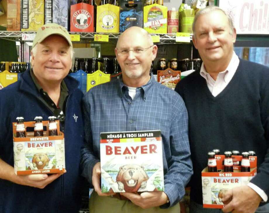 Baxter Urist, founding partner of Beaver Beer Co. LLC, left, stands with Jack Riley, owner of Greens Farms Spirit Shop, center, and Bill O'Brien, Beaver Beer's president and chief executive officer, right, with the company's different types of craft beer. Greens Farms Spirit Shop is one of about 120 locations carrying the brand throughout Fairfield and New Haven counties, the fledgling company's test market. Photo: Contributed Photo