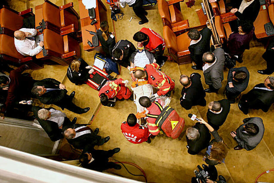 Paramedics attend to Adrian Sobaru, an electrician at the national television station who threw himself from a balcony in Romania's Parliament on Thursday, Dec. 23, 2010 just as the prime minister began to speak ahead of a no-confidence vote. Sobaru suffered fractures to the face, and other non life-threatening injuries, according to a hospital official. Photo: CC Otiliu, AP