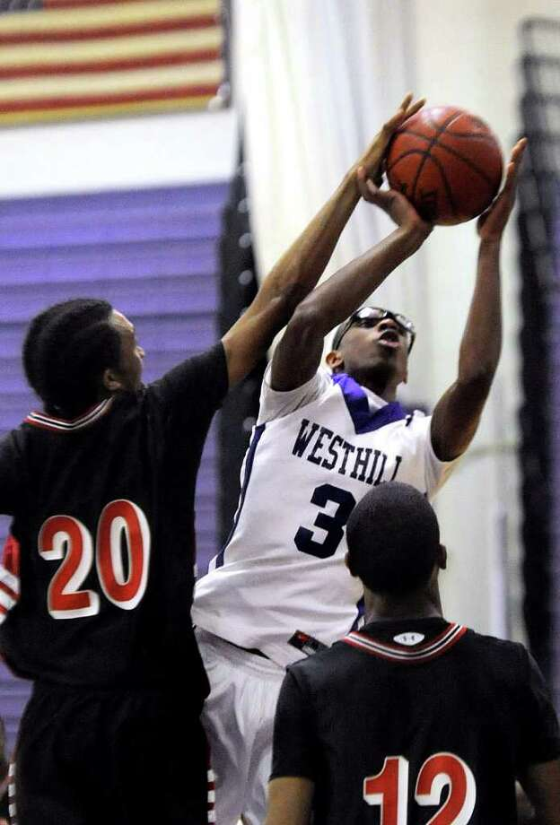 Westhill's Chris Walters is defended by Bridgeport Central's Robert Blackwell, left, and Josh Wilerson, right, at Westhill High School in Stamford on Friday, January 13, 2012. Photo: Lindsay Niegelberg / Stamford Advocate