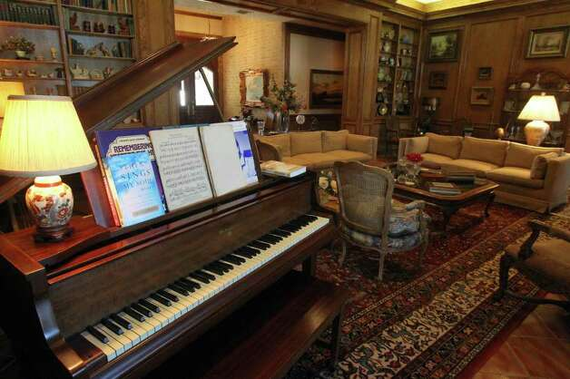 The great room has a baby grand piano and is flush with wood paneling. Photo: JOHN DAVENPORT/jdavenport@express-news.net, SAN ANTONIO EXPRESS-NEWS