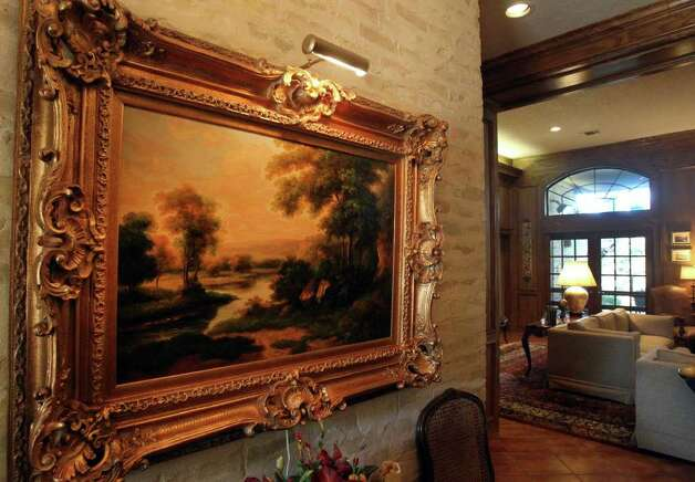 Lovely landscape paintings with lighting adorn the walls in the foyer area of the home. Photo: JOHN DAVENPORT/jdavenport@express-news.net, SAN ANTONIO EXPRESS-NEWS