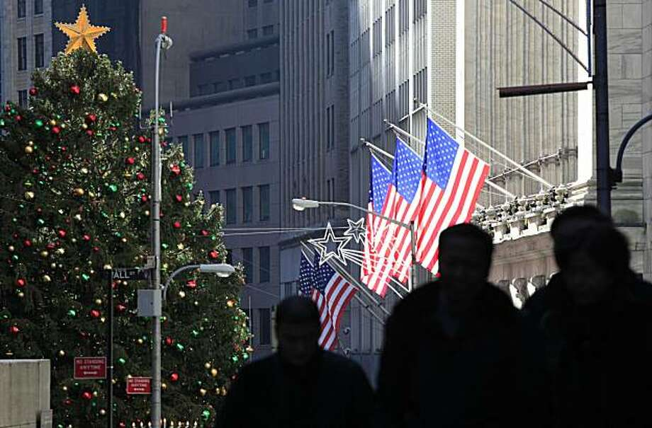 People walk in New York's financial district near the flag-draped New York Stock Exchange, Wednesday, Dec. 22, 2010 in New York. Photo: Mark Lennihan, AP