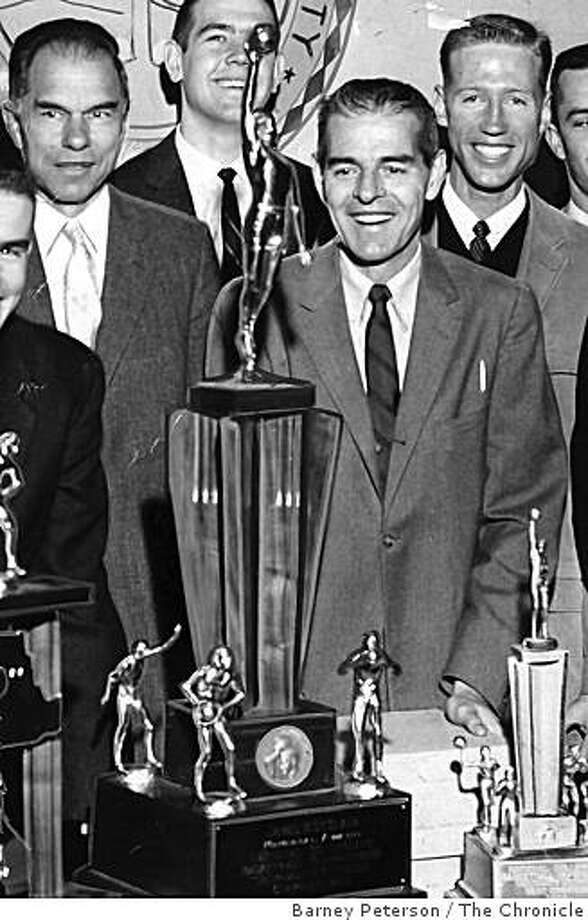 Pete Newell, to right of the big NCAA championship trophy, stands next to UC Berkeley Chancellor Glenn Seaborg, left, on March 23, 1959 after Cal won the 1959 NCAA men's basketball championship. Photo: Barney Peterson, The Chronicle