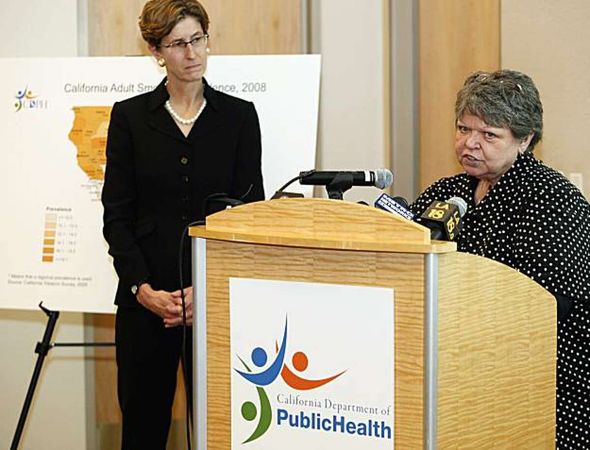 Tobacco educator and motivational speaker Debi Austin, right, at podium , with California Health and Human Services Agency, secretary, Kimberly Belshe, left, comments on the negative effects of tobacco during a news conference unveiling a series of anti-tobacco television advertisements today by the California Department of Public Health at the California Endowment Center for Healthy Communities in Los Angeles on Monday, Dec. 20, 2010.