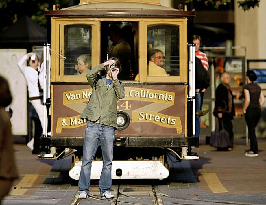 Cable car riders photograph the California Street tracks from Drumm Street in downtown San Francisco on Sunday, Sept. 30, 2007. Tourism is San Francisco's leading industry, generating $7.3 billion in 2006.  Photo by Kim Komenich/San Francisco Chronicle Photo: Kim Komenich, The Chronicle
