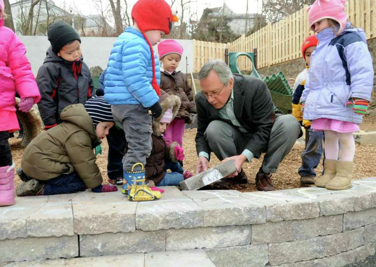 Family Centers President and CEO Bob Arnold fixes a brick on the playground at the nonprofit's Arch Street headquarters in Greenwich Wednesday, Jan. 11, 2012. Arnold is marking his 30th year working with the organization, which offers education and human services to children, adults and families in Fairfield County.