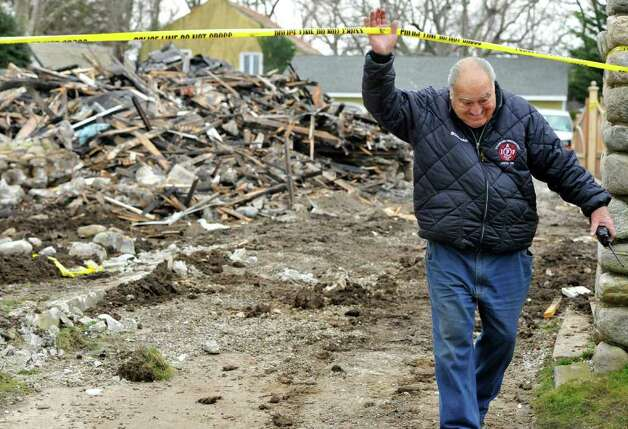 Stamford fire department Lt. Tommy Mardi leaves the charred remains of Madonna Badger's home in Stamford, Conn., Tuesday, Dec. 27, 2011.   A fire killed Badger's three daughters and parents early Christmas morning.  (AP Photo/Jessica Hill) Photo: Jessica Hill, Associated Press / AP2011