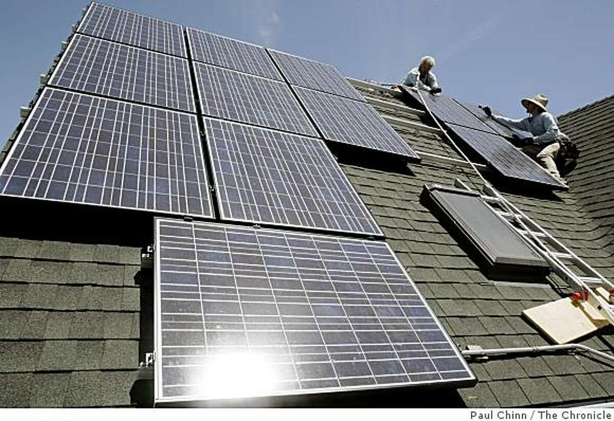 Tom Peterson (left) and Peter Gregory install solar panels on Benjamin Yee's home in Emeryville, Calif. on Tuesday, July 17, 2007. Yee says he's the first homeowner to go solar in Emeryville.