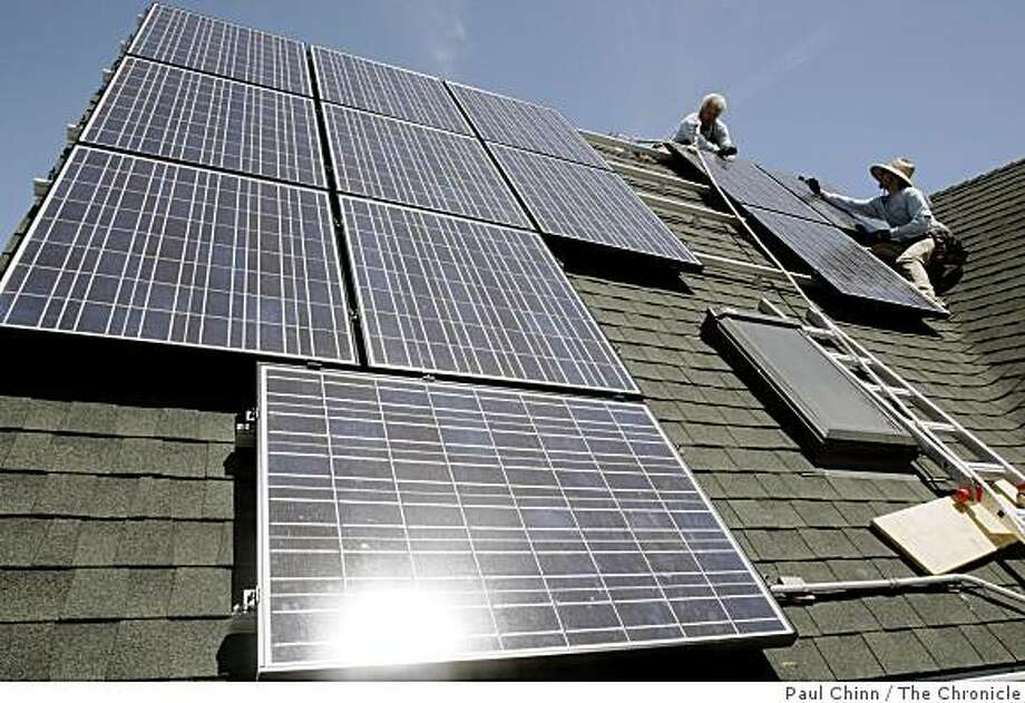 Tom Peterson (left) and Peter Gregory install solar panels on Benjamin Yee's home in Emeryville, Calif. on Tuesday, July 17, 2007. Yee says he's the first homeowner to go solar in Emeryville. Photo: Paul Chinn, The Chronicle