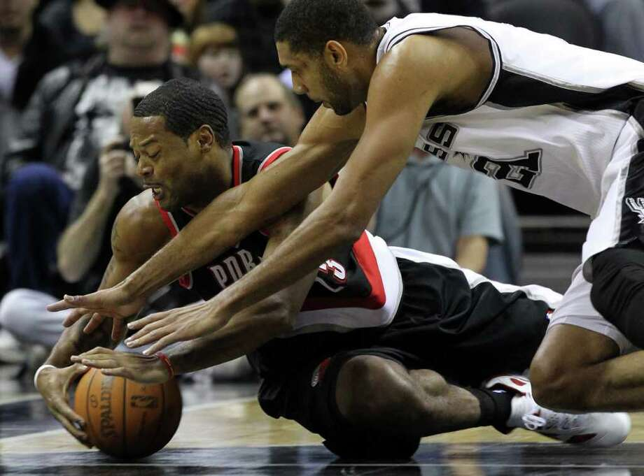 Spurs' Tim Duncan (right) dives for a loose ball with Portland Trailblazers' Marcus Camby in the first half at the AT&T Center on Friday, Jan. 13, 2012. Photo: KIN MAN HUI, ~ / San Antonio Express-News