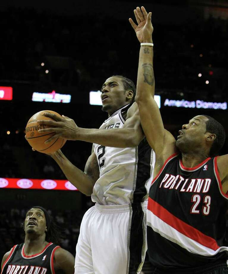 Spurs' Kawhi Leonard (02) drives to the basket against Portland Trailblazers' Marcus Camby (23) in the first half at the AT&T Center on Friday, Jan. 13, 2012. Photo: KIN MAN HUI, ~ / San Antonio Express-News