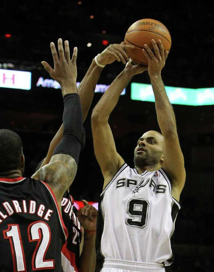 Spurs' Tony Parker (09) gets his shot tipped by Portland Trailblazers' Marcus Camby (23) as LeMarcus Aldridge (12) closes ranks in the first half at the AT&T Center on Friday, Jan. 13, 2012. Photo: KIN MAN HUI, ~ / San Antonio Express-News