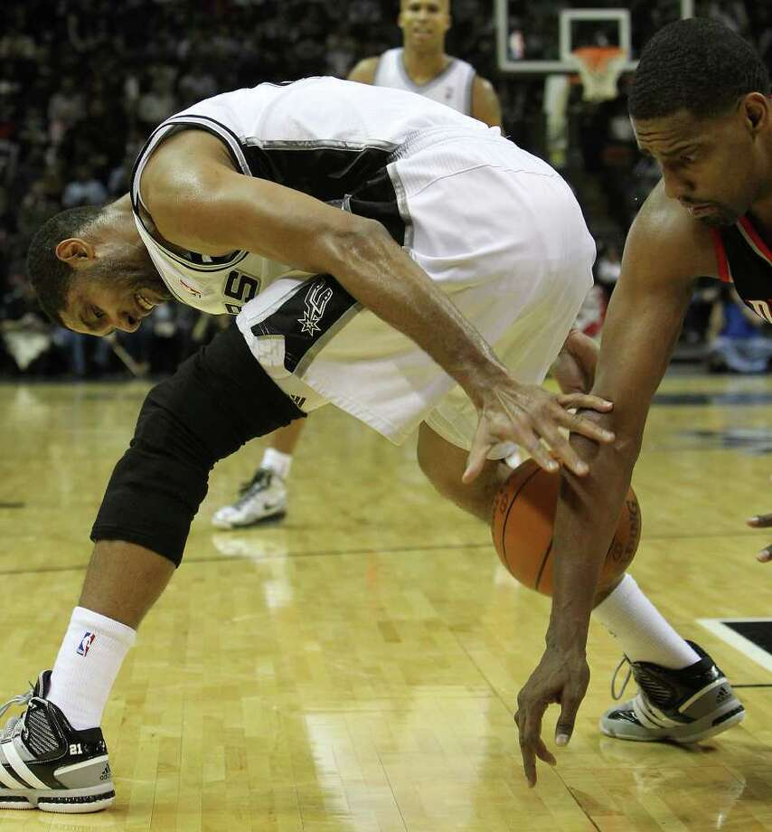 Spurs' Tim Duncan (left) tries to regain control of the ball against Portland Trailblazers' Kurt Thomas (40) in the second half at the AT&T Center on Friday, Jan. 13, 2012. Spurs defeated the Trailblazers, 99-83. Photo: KIN MAN HUI, ~ / San Antonio Express-News