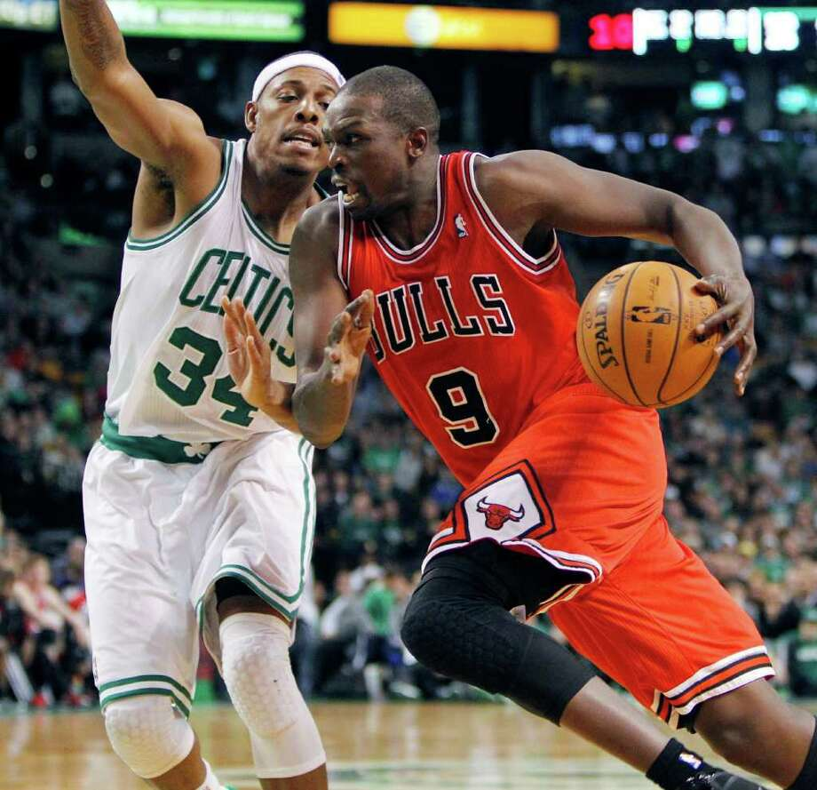 Chicago's Luol Deng (9) drives past Boston's Paul Pierce in the fourth quarter Friday. Deng had 21 points and 16 rebounds. Photo: AP