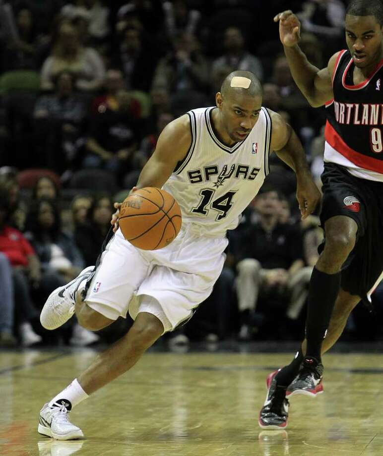 Spurs' Gary Neal (14) pushes the ball upcourt against Portland Trailblazers' Elliot Williams (09) in the second half at the AT&T Center on Friday, Jan. 13, 2012. Neal had a bandage on his head from an off-court injury. Spurs defeated the Trailblazers, 99-83. Photo: KIN MAN HUI, ~ / San Antonio Express-News