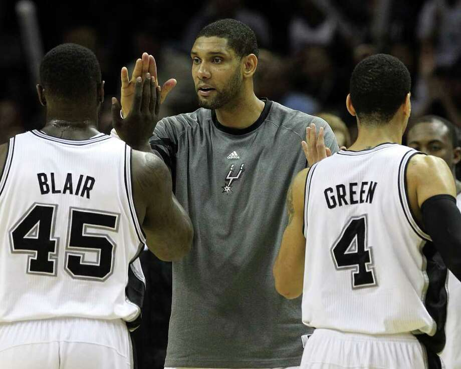 Spurs' Tim Duncan (center) greets teammates DeJuan Blair (left) and Danny Green (right) at a timeout in a game against Portland Trailblazers in the second half at the AT&T Center on Friday, Jan. 13, 2012. Spurs defeated the Trailblazers, 99-83. Photo: KIN MAN HUI, ~ / San Antonio Express-News