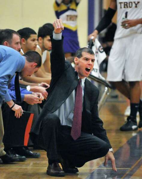 Troy High coach Richard Hurley calls to his players during Friday's game against Bishop Gibbons at T