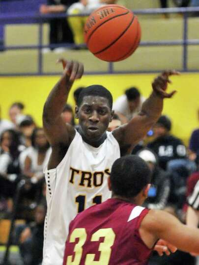 Troy High guard Trahmier Burrell, top, gets a pass over Bishop Gibbons' #33 Jonathan Villanueava dur