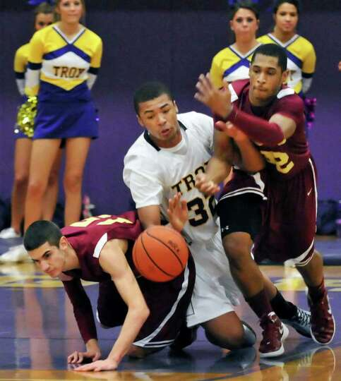Troy High 's #32 Javion Ogunyemi gets sandwiched between  Bishop Gibbons' #15 Kyle Garrison, left, a