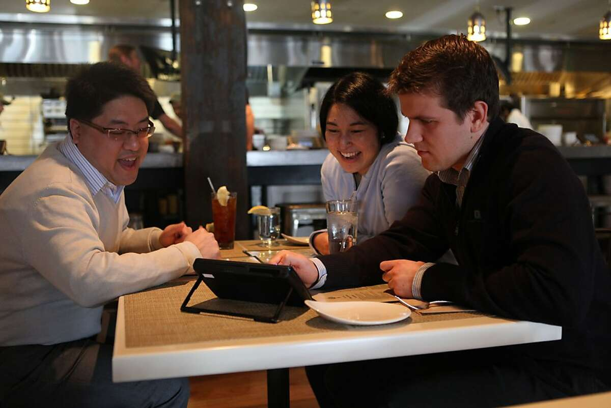 Sidney Chen (far left), Cindy Matsuyama (middle), and Ivan Tsurikov (right) look over a new tablet that restaurants can put at every table for do-it-yourself ordering, paying the bill, and playing games while at Calafia in Palo Alto, Calif., on Wednesday, January 11, 2012.