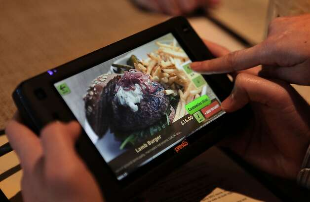 Patrons scroll a new tablet that restaurants can put at every table for do-it-yourself ordering and paying the bill at Calafia in Palo Alto, Calif., on Wednesday, January 11, 2012. Photo: Liz Hafalia, The Chronicle