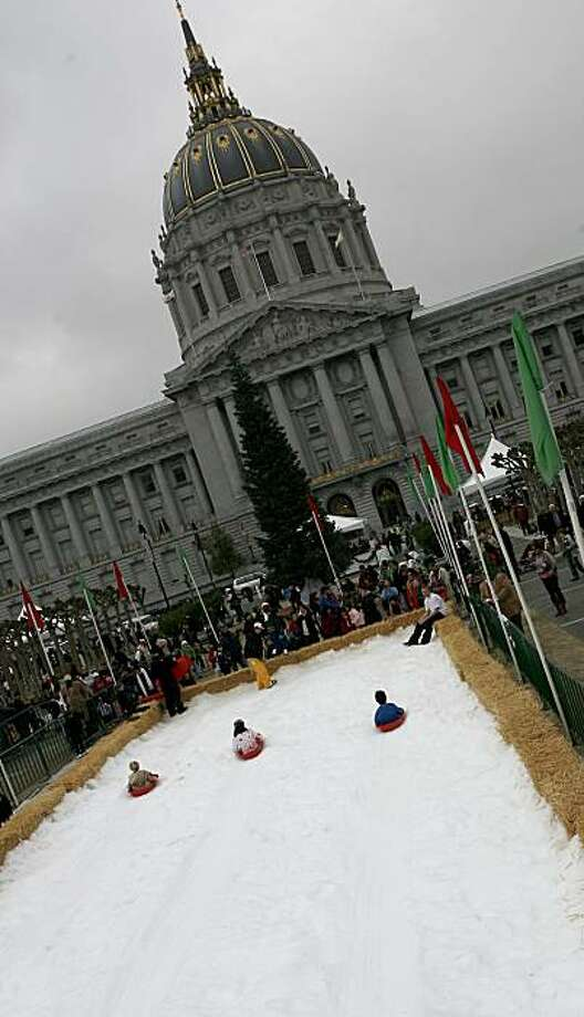 Children enjoy the slope at San Francisco City Hall's holiday open house Sunday. Photo: Kirsten Aguilar, The Chronicle