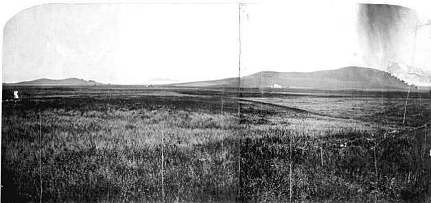 """A famous 1861 photo by photographer Carleton Watkins taken for documentation in the Federal land cases of Domingo Peralta, still being decided in the US court, even though the land became US territory at the end of the Mexican American War in 1848. Note the hills of Flemming Point on the far left and Albany Hill on the far right. The large structure in front of the left side of Albany Hill is the Wilson Road House, used by gold miners and ranch hands as a hotel, gambling hall and saloon and horse-watering hole. It was also known as the Seven Mile House, being seven miles from downtown Oakland. Hotels on this route were named in this fashion, as the ferry wharf in Oakland was where many gold miners got off at to begin their trek to the Sierras and the gold fields. Captain Bowen's Roadhouse, one of the earliest American structures in West Berkeley, established in 1853 at the northwest corner of San Pablo Avenue and Delaware Street, was known as the Six Mile House.  Note the flatlands filled with fragrant tarweed. From the book """"Eccentrics, Heroes, and Cutthroats"""" by Richard Schwartz. Photo: Courtesy Richard Schwartz"""